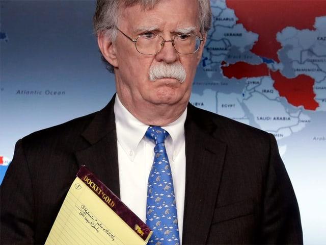 John Bolton mit ernstem Blick und dem gelben Notizblock unter dem Arm.