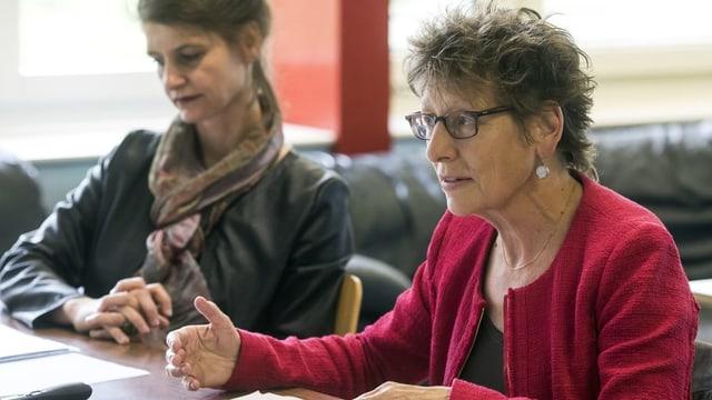 Zwei Frauen an Tisch.