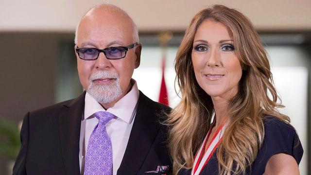 René Angélil und Celine Dion Halbnahe lachen in Kamera. Er mit Brille, Anzug und violetter Krawatte. Sie im schwarzen Oberteil und Medaille um Hals.