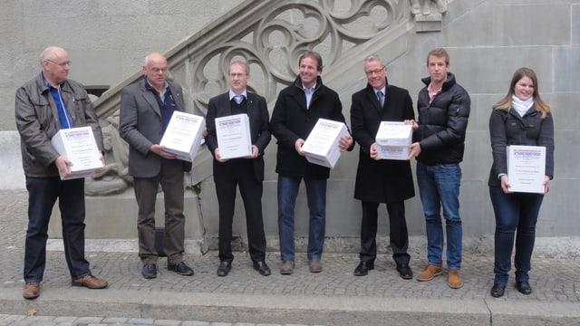 Sechs Männer und eine Frau mit Schachteln vor dem Berner Rathaus
