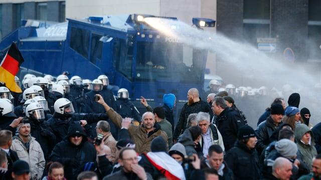 Ein Wasserwerfer der Polizei im Einsatz gegen Pegida-Demonstranten
