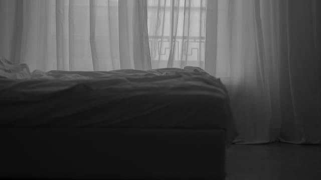 Bett mit weissem Bezug und weissen Vorhängen vor dem Fenster