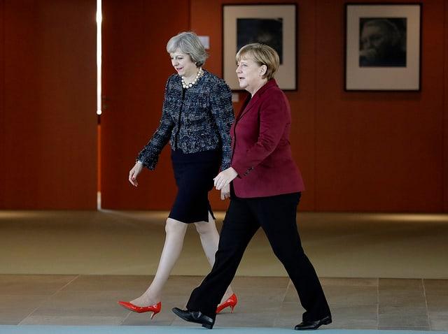 Zu sehen sind die beiden Regierungschefs Angela Merkel sowie Theresa May.