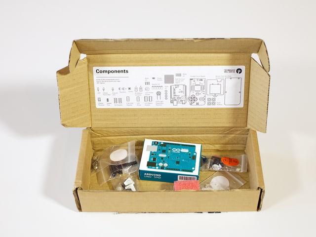 Eine offene Kartonschachtel mit Elektronikbauteilen.