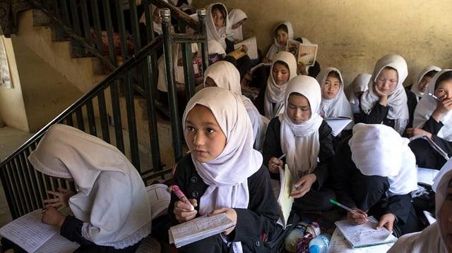 Mädchen mit weissen Kopftüchern sitzen mit ihren Schreibheften und -stiften in einem Treppenhaus.
