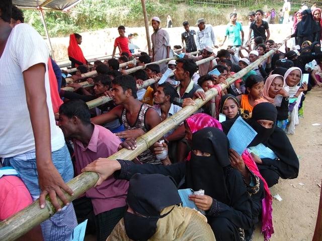 Dutzende Menschen sitzen hintereinander zwischen Bambusstangen, welche die Warteschlange ordnen.