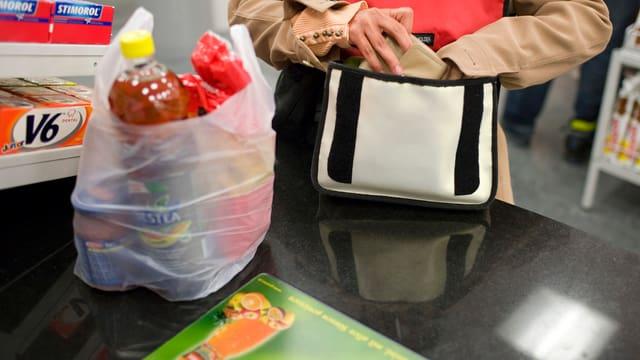 Plastiksäcklein mit Einkauf an Ladenkassse