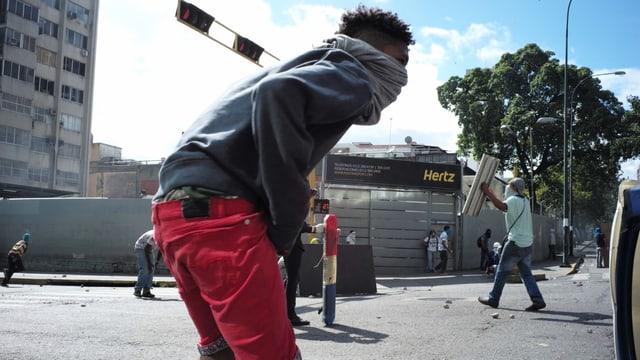 Ein junger Mann mit verhülltem Gesicht steht auf der Strasse. Im Hintergrund andere Protestierende.
