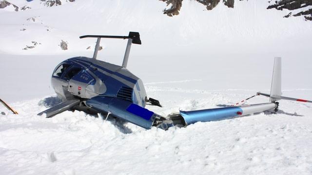 Der blaue Hubschrauber liegt seitlich gekippt im Schnee. Er ging bei der Landung in die Brüche.