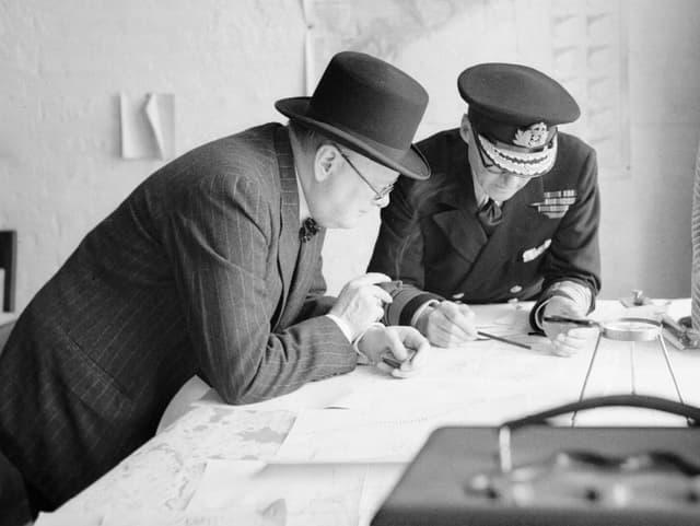 Zwei Männer beugen sich über Unterlagen.