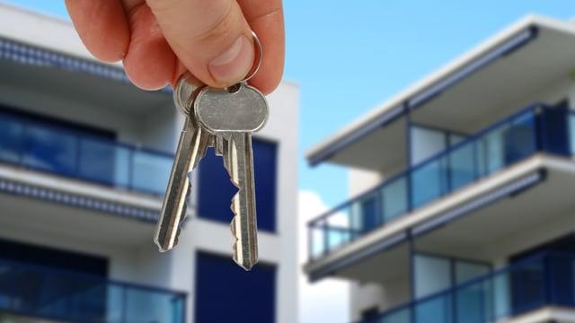 Jemand hält Schlüssel vor einem neuen Haus.