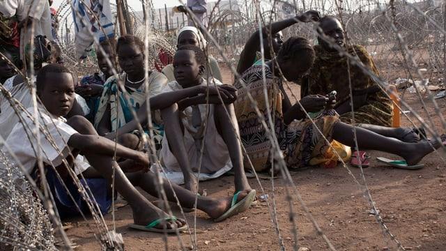 Flüchtlinge von der ethischen Gruppe der Nuer warten in einem Lager auf Essen.