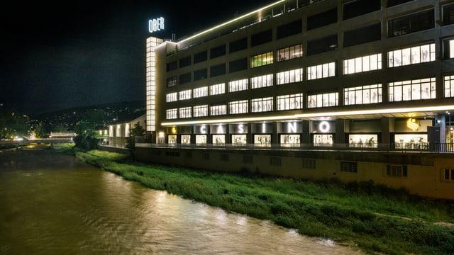 Ein Fluss bei Nacht, daneben ein fünfstöckiges Gebäude.