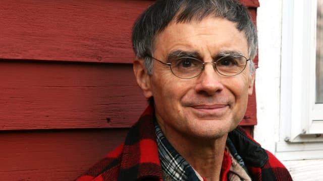 Ein Mann mit Brille vor einer roten Hauswand.
