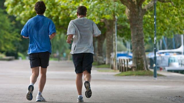 Zwei Männer mit verschwitzten T-Shirts rennen entlang einem See.