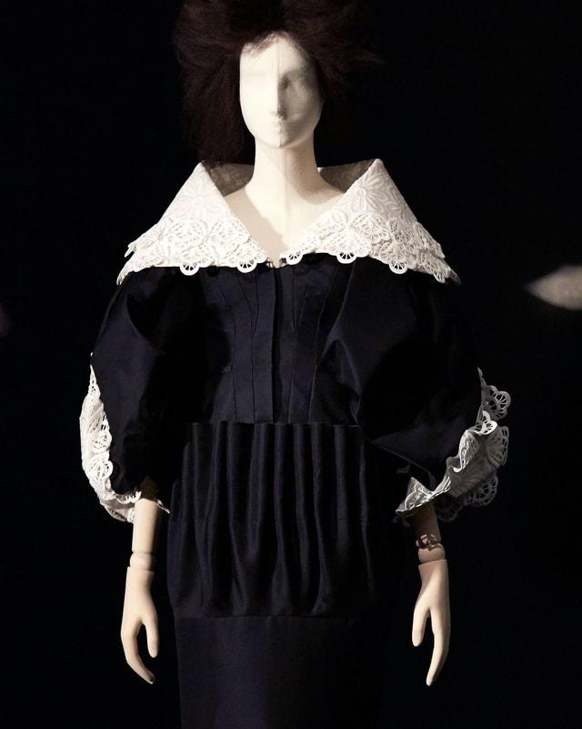 Schwarzes Kleid mit weissen Spitzen an Ärmeln und Kragen.