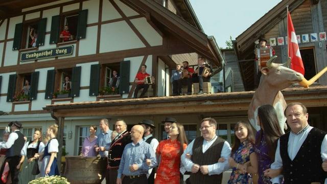 Schunkelde Menschen vor Landgasthof mit Musikanten die aus Fenstern herausschauen.