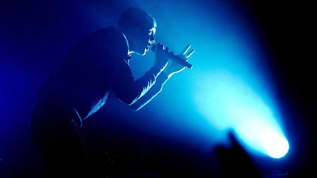 Ein Sänger mit Mikrofon in der Hand in blauem Scheinwerferlicht.