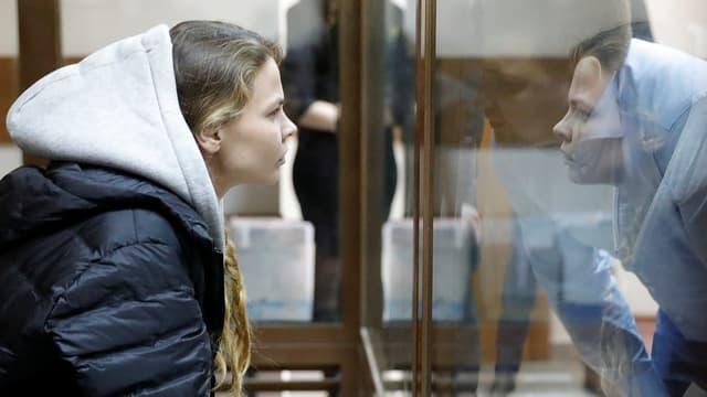 Waschukewitsch blickt durch eine Scheibe und spricht mit einem Mann.