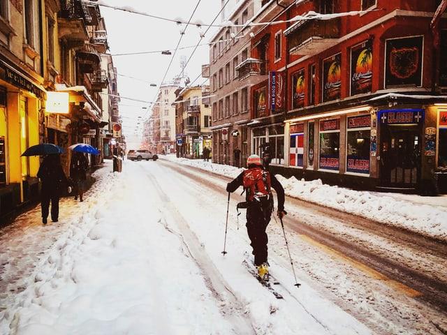 Eine Person auf Skis auf der verschneiten Langstrasse in Zürich.