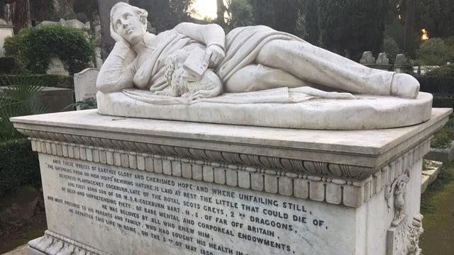 Ein Grabstein mit der Skulptur eines Mannes.