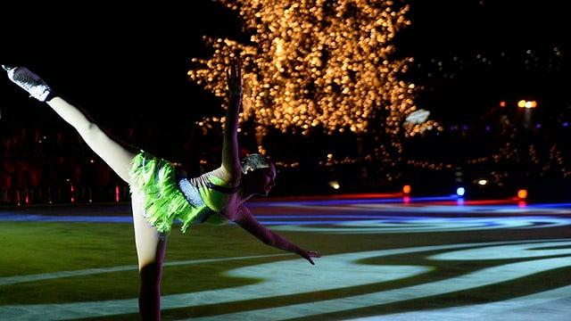 Schlittschuhläuferin vor einem Weihnachtsbaum.