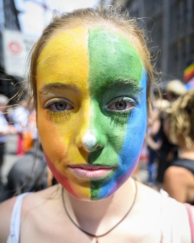 Eine junge Frau mit in Regenbogenfarben angemaltem Gesicht blickt in die Kamera.