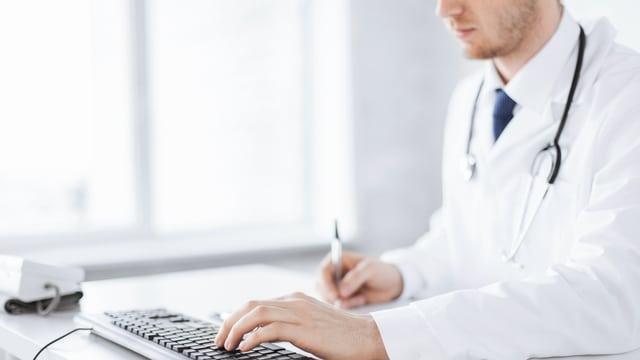 Ein Arzt gibt Daten in einen Computer ein (Symbolbild).