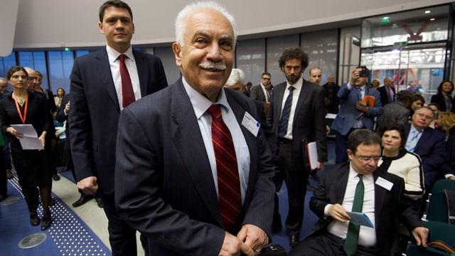 Der Genozid-Leugner Dogu Perincek geht durch einen Raum des Gerichtshofs, rund um ihn andere Leute.