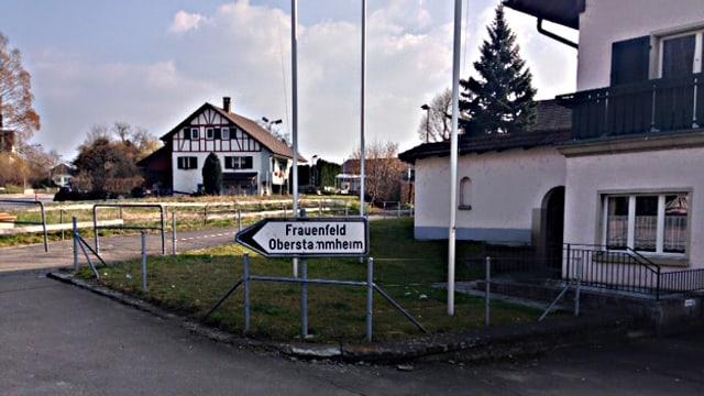 Wegweiser mit der Aufschrift Frauenfeld Oberstammheim, im Hintergrund ein Weinländer Bauernhaus in der Sonne