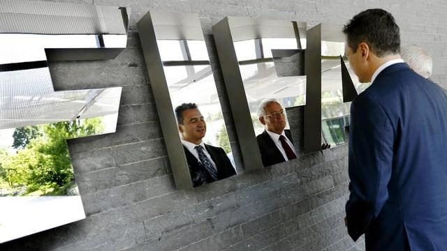 Garcia und Eckert vor dem FIFA-Logo, im welchem sich ihre Gesichter spiegeln.
