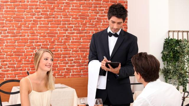 Ein Paar gibt dem Kellner eine Bestellung auf.