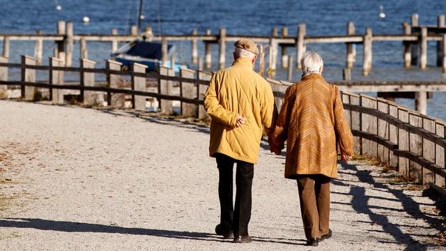 Ältere Mann und ältere Frau spazieren am See