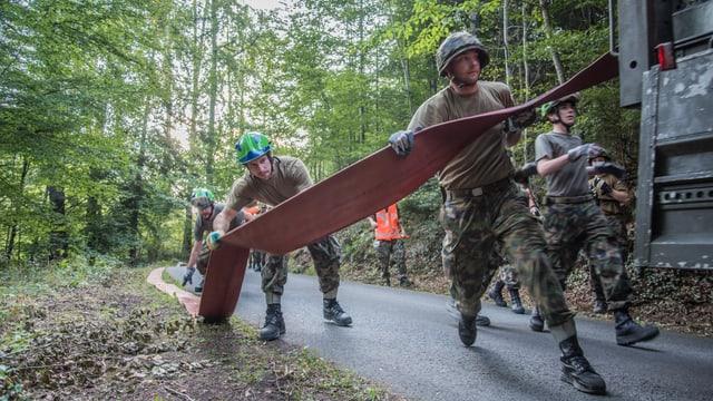 Militär rollt Wasserschläuche ab.
