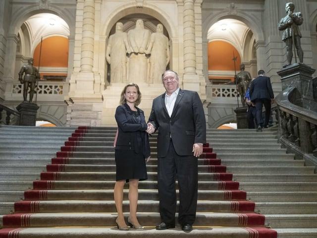 Frau und Mann geben sich die Hand auf der Treppe im Eingangsbereich des Bundeshauses.