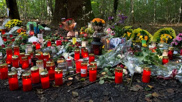 Kerzen und Blumen im Wald am Boden.
