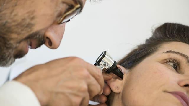 Ein Arzt untersucht das Ohr einer Patientin.