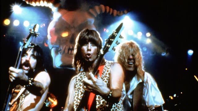 Drei Männer mit langen Haaren und Gitarren auf einer Bühne