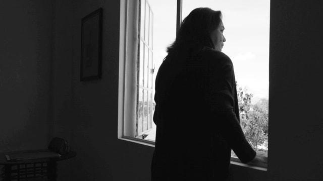 Frau steht am Fenster und blickt nach draussen.