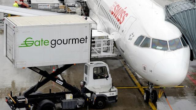 """Aus einem zur Flugzeugtür hochgefahrenen Container mit der Aufschrift """"Gategourmet"""" wird Essen in ein am Gate geparktes Swiss-Flugzeug eingeladen."""