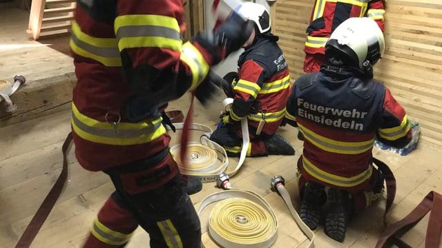 Männer in Feuerwehruniform mit Schläuchen.