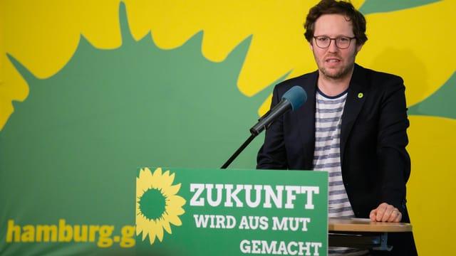 Mann mit Brille an einem Rednerpult, Dahinter das Grünen-Logo.