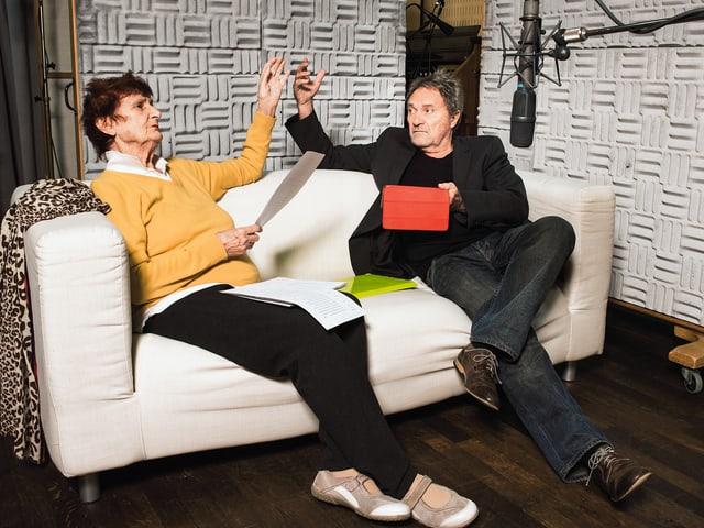 Eine Frau und ein Mann sitzen auf einem Sofa. Sie halten beide theatralisch einen Arm in die Luft.