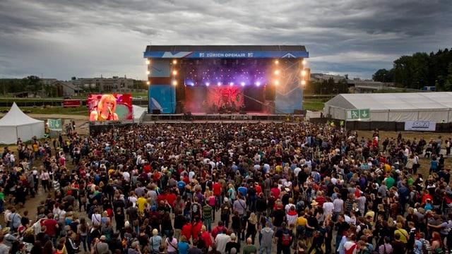 Im Hintergrund sieht man eine Konzertbühne auf freiem Feld, im Vordergrund das Publikum.