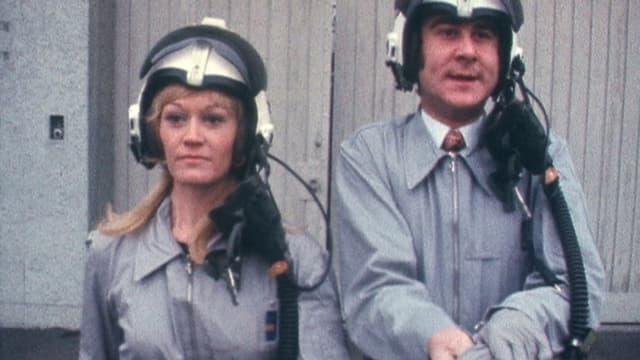 Rosemarie Pfluger und Kurt Felix in «Grüezi mitenand» mit Helm und Rennanzug.