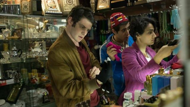 Armand probiert in einem Laden Handschuhe an, die zur Burka passen sollen.