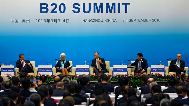 Ina runda da discussiun sin in palc sut il logo dal B20 summit.
