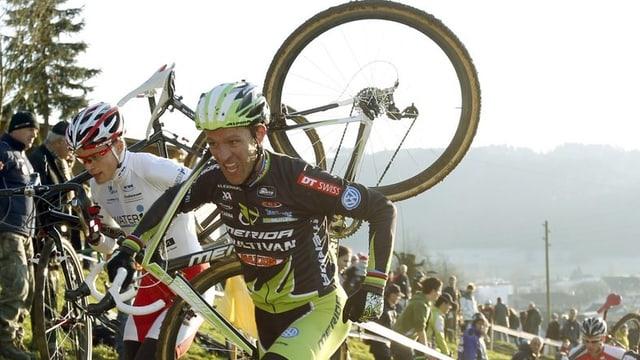 Ralph Näf rennt mit dem Bike auf dem Buckel einen Hang hinauf.