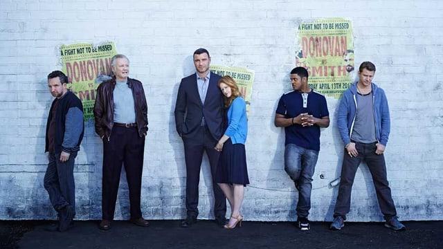 Sechs Personen, fünf Männer und eine Frau, stehen vor einer Wand.