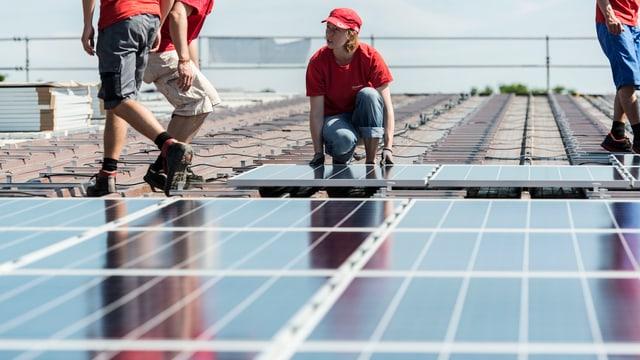 Eine Frau montiert ein Solarpanel auf einem Dach.